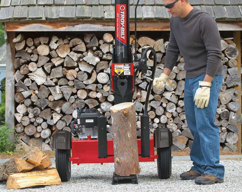 man carrying log walking towards Troy-Bilt log splitter in wooded area