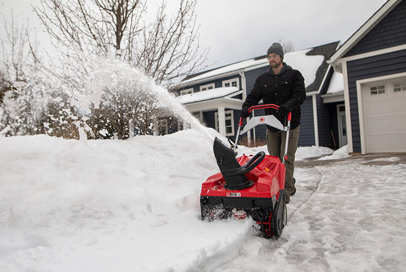 Man clearing snow by pile with single stage snow blower