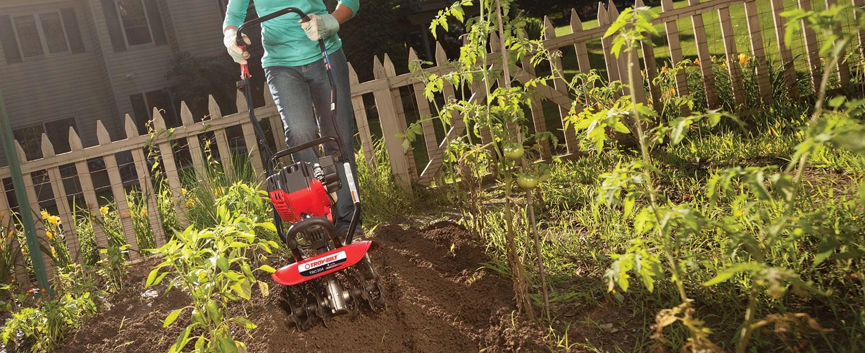 woman tilling her backyard garden