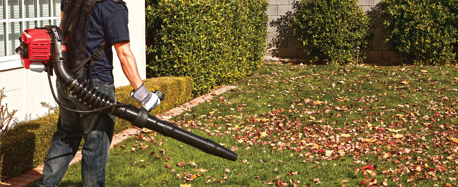 man using Troy-Bilt backpack leaf blower on lawn