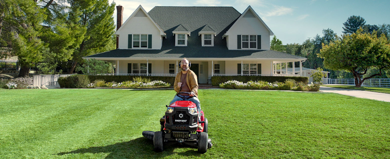 man on riding lawn mower with headphones