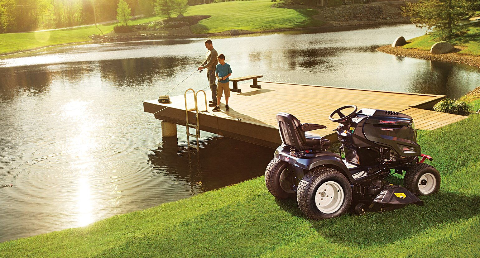 man on pier and riding lawn mower
