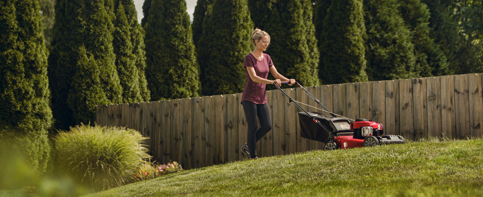 woman mowing her lawn with walk-behind mower
