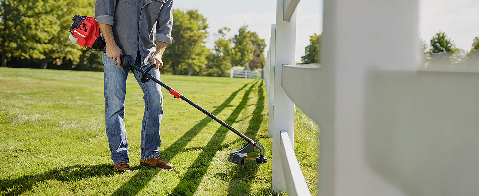 man trimming lawn close to white wooden fence