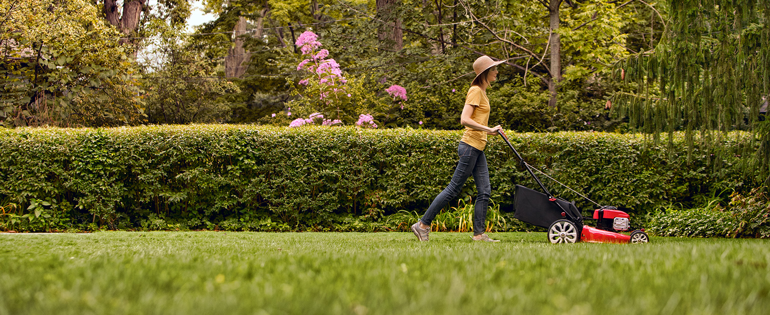 woman mowing her backyard garden