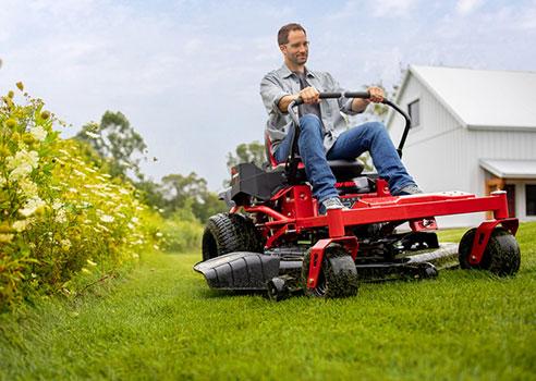 man riding troy-bilt zero-turn riding lawn mower on yard