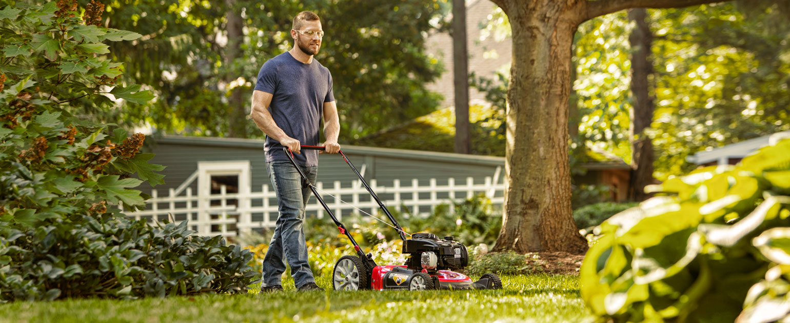 man mowing his backyard with walk-behind mower