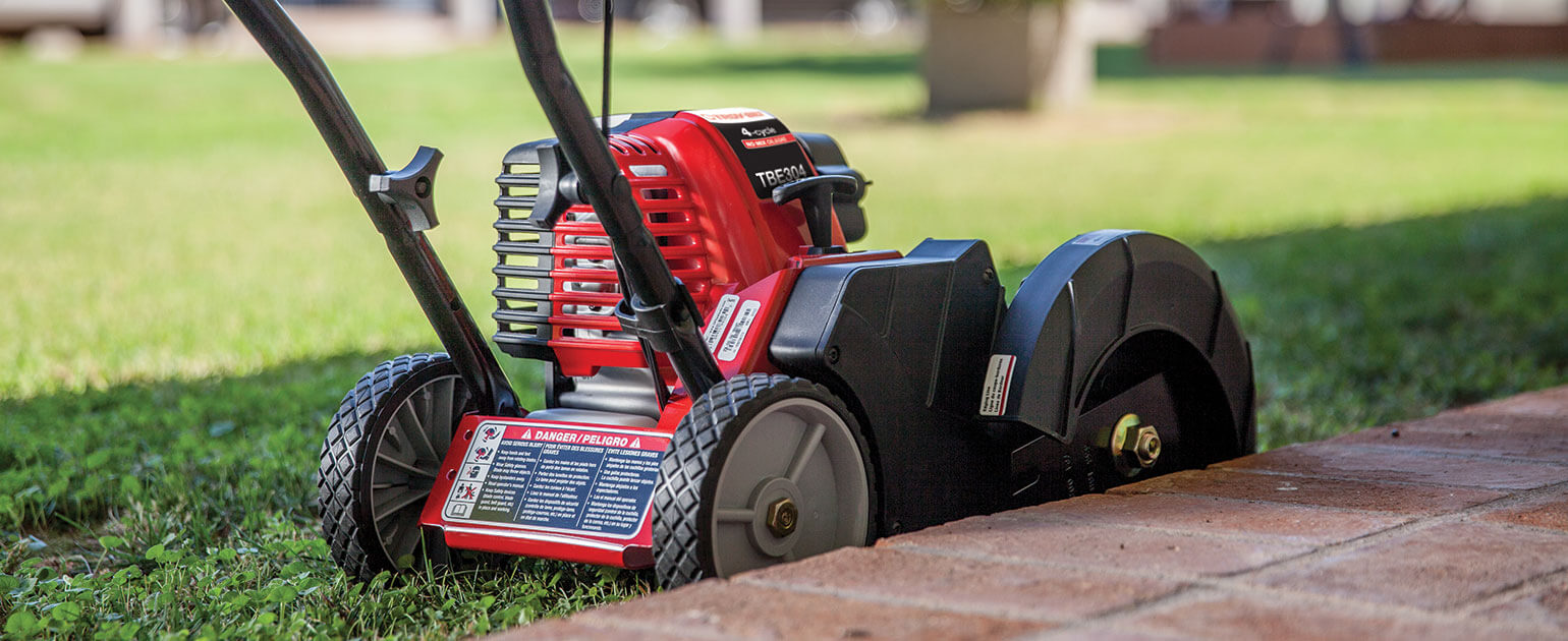 Troy-Bilt edger being used to edge grass beside brick patio