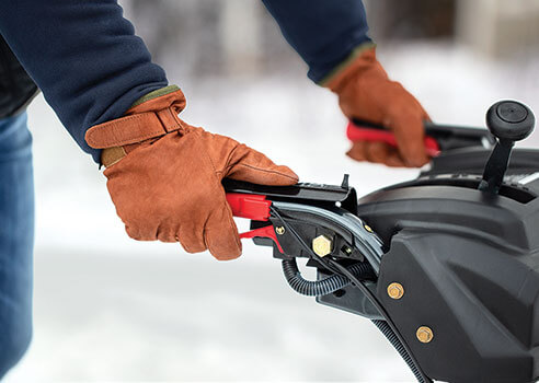 person holding the heated hand grips on a snow blower