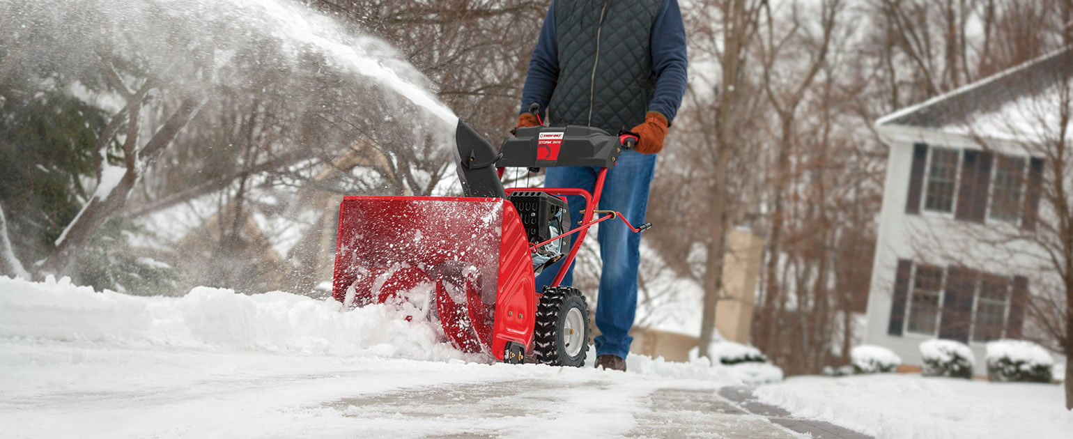 Person using two-stage snow blower on lane-way