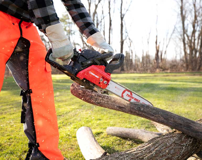 man cutting fallen limbs in wooded area