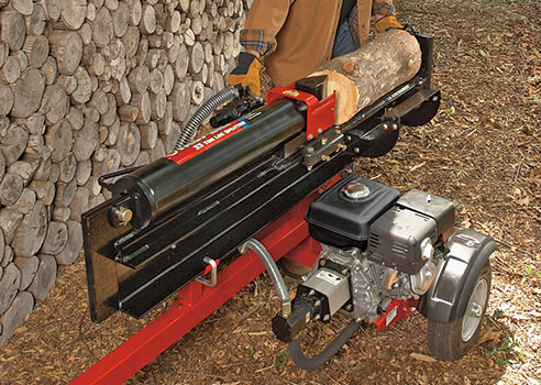 person using log splitter in front of wall of stacked wood logs