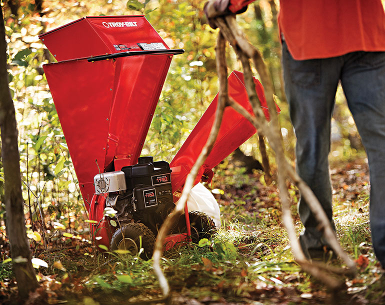 man carrying branches walking towards Troy-Bilt Chipper Shredder in wooded area