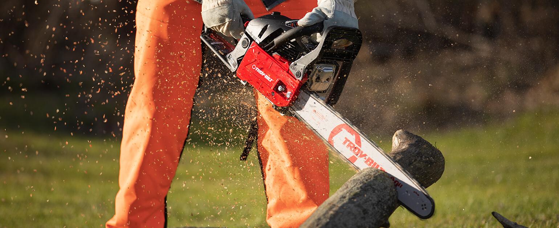 man cutting through a piece of wood