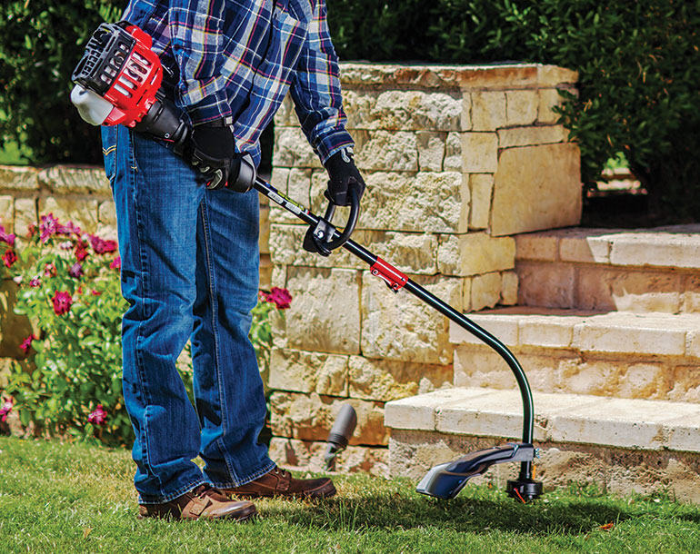 man trimmer grass by the bottom of stone steps