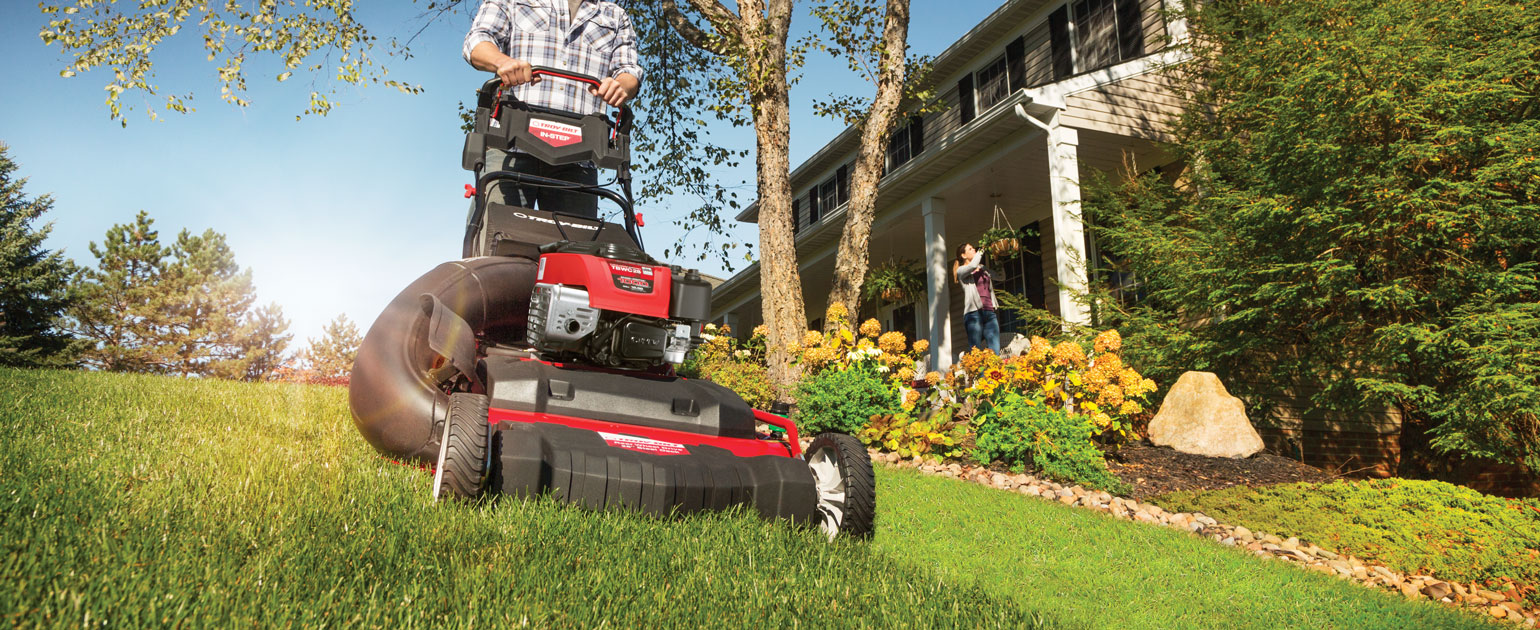 Person cutting their lawn with a Troy-Bilt Wide-Area push mower